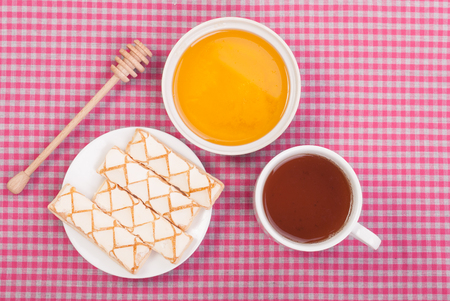 tea and biscuits: Tea biscuits and honey on the tablecloth. Stock Photo