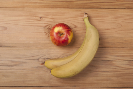 Apple and ripe bananas lie on a wooden background.