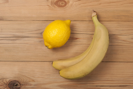 Lemon and bananas on a wooden background. View from above .