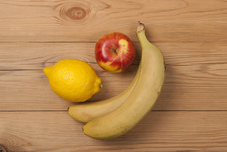 Lemon apple and bananas on a wooden background. View from above .