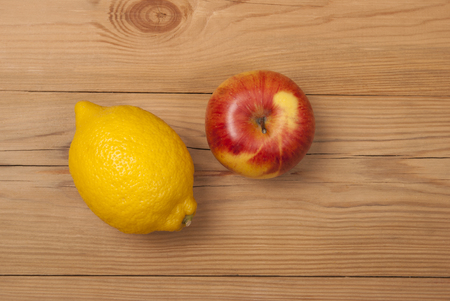 Lemon and apple on a wooden background. View from above . Фото со стока