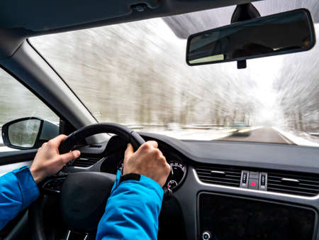 the car quickly drives along a slippery road in a snowy forest. Inside view of a car. Hands of the driver on the steering wheel. Stock Photo