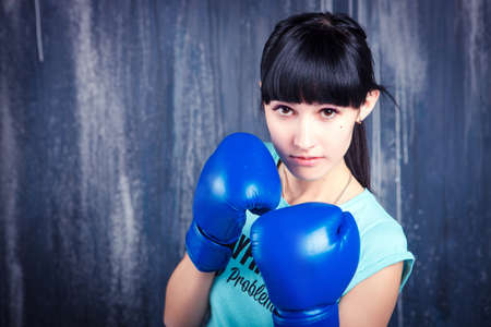 the young sports girl with dark hair in boxing gloves