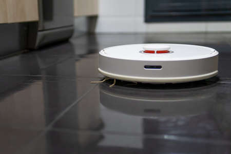 robot vacuum cleaner cleaning the kitchen floor