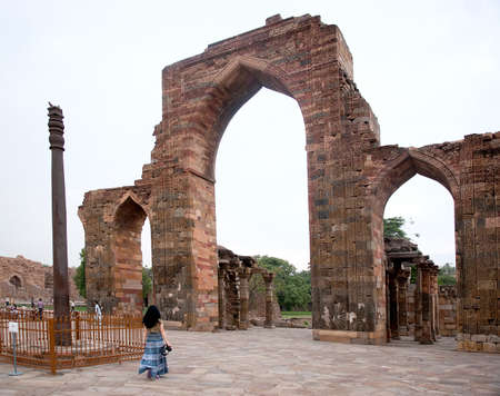 Women visit Iron Pillar at Qutub Minar in Delhi, India.  Iron Pillar made of 98% wrought iron and has stood 1,600 years without rusting or decomposing.