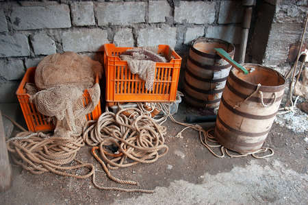 fishermans net: Fishermans storage. Old two wooden barrels, net stored in fish crates, ropes. Stock Photo