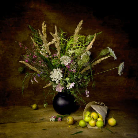 Summer bouquet  with wild flowers and pears on the wooden table with natural light. Still life looking like a painting.