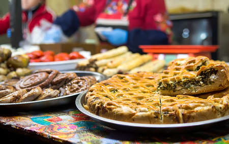 Assortment of fragrant pies, grilled sausages sold on Christmas market. Winter holidays outdoors. Selective focus Stock Photo