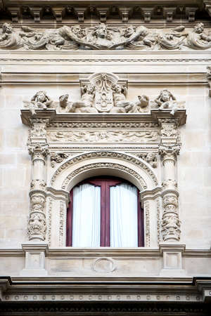 Window decorated with carving and sculptures in neo-baroque style Banco de Imagens