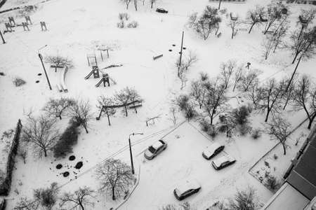View from above to the yard of residential building after snowfall with snow covered cars. Selective focus
