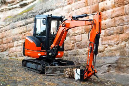 Small machine res excavator on sidewalk during repair works on street in urban environment