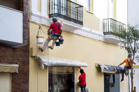 Workers paints building wall, renovating works