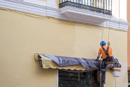 Trabajador pinta la pared del edificio, obras de renovación Foto de archivo