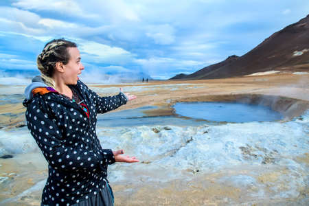 Young woman enjoying the view of geothermal bath in Iceland. Selective focus