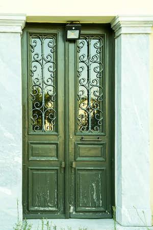 Casa tradicional puerta de madera blanca con molduras de piedra y rejillas de hierro artesanales en la pared Foto de archivo