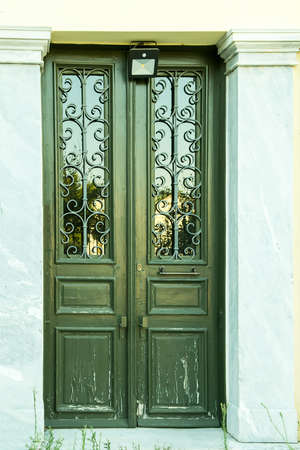 Traditional house white wooden door with stone trim and handcrafted iron grilles on wall Banco de Imagens