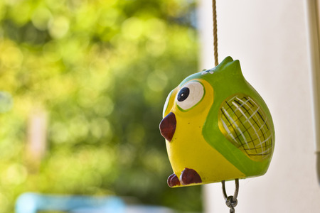 Close up handicraft ceramic bell with green nature background