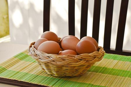 brown eggs: Raw organic brown eggs in wicker basket put on bamboo mat Stock Photo
