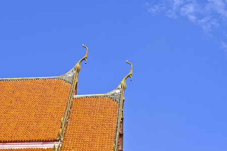 Roof style of Thai temple with gable apex on the top with blue sky Stock Photo