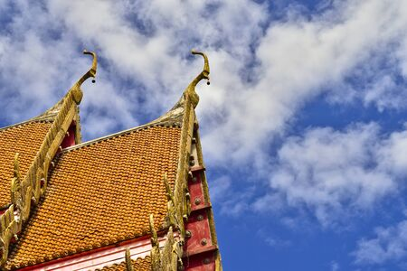 Roof style of Thai temple with gable apex on the top with blue sky and white cloud Stock Photo