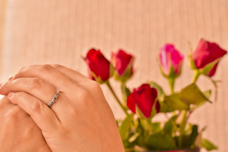 Wedding ring in woman hands with red and pink rose background, Valentine's Day, moment in love, will you marry me