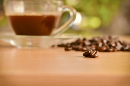 odorous: scattered roasted coffee beans on wooden table and a cup of coffee background