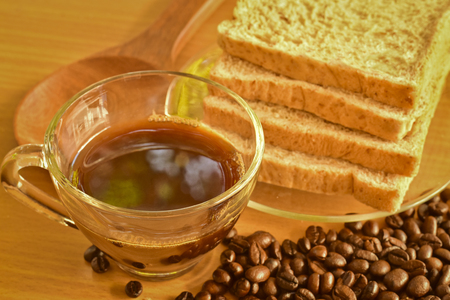 odorous: Coffee cup with whole wheat bread and scattered roasted coffee beans on Wooden Table