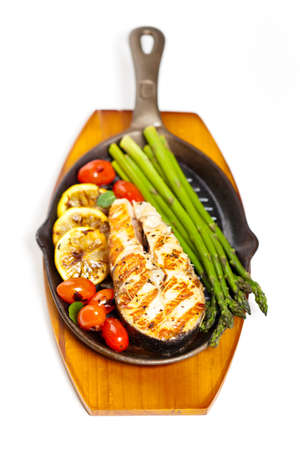 Grilled salmon steak with asparagus and cherry tomatoes photo