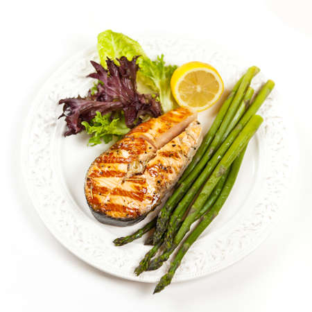 Grilled salmon steak with asparagus, lemon and salad photo