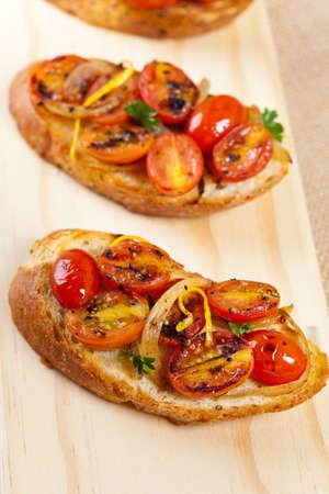 Italian Bruschetta with baked cherry tomatoes and onion photo
