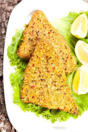 Fried breaded tilapia fish fillet and lemon on white plate  photo
