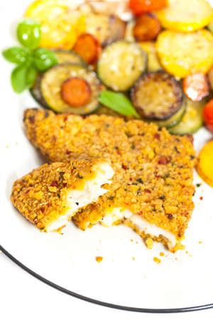 Fried tilapia fish fillet with vegetables on white plate  photo