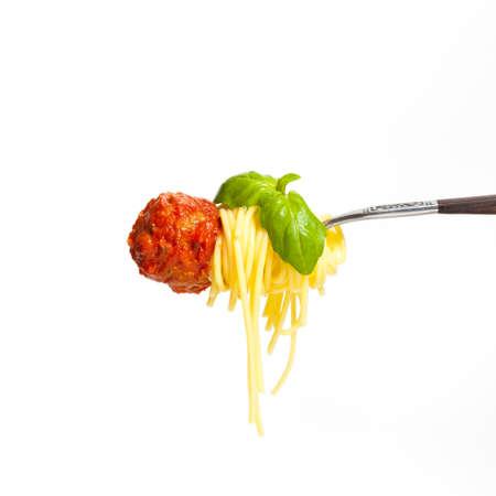 Gehaktbal met spaghetti en basilicum op een vork Stockfoto