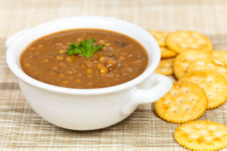 A cup of lentil soup with saltine crackers