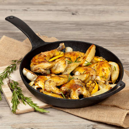 Garlic, Lemon and Rosemary Roasted Chicken on Frying Pan with potato  Selective focus  Stock Photo