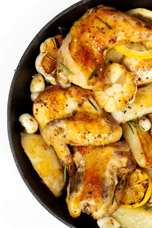 Garlic, Lemon and Rosemary Roasted Chicken on Frying Pan with potato  Selective focus  photo