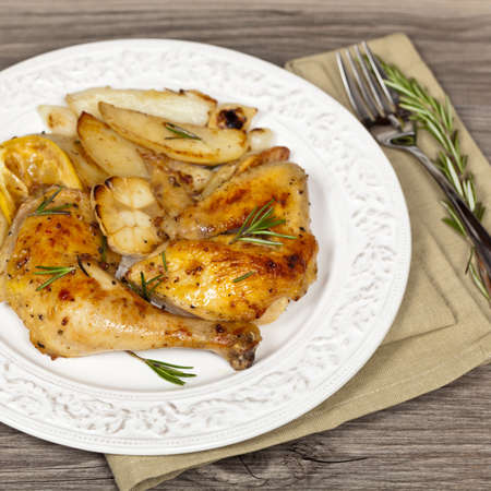 Roasted Chicken with Garlic, Lemon and Rosemary with potato  Selective focus  photo