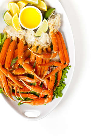 Snow Crab legs with fresh lemon slices and butter sauce photo