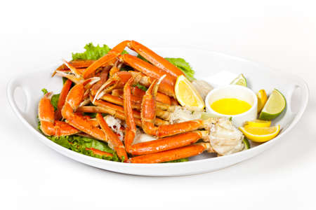 cangrejo: Las patas de cangrejo de nieve con rodajas de limón fresco y salsa de mantequilla Foto de archivo