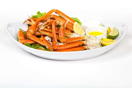 cangrejo: Las patas de cangrejo de nieve con rodajas de lim�n fresco y salsa de mantequilla Foto de archivo