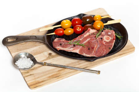 Raw lamb chops with cherry tomato and rosemary herb ready to cook  Selective focus  photo