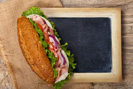 Deli sub sandwich with chalkboard. Selective focus. photo