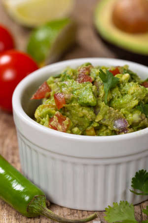 Guacamole with avocado, lime, tomato and cilantro Stock Photo