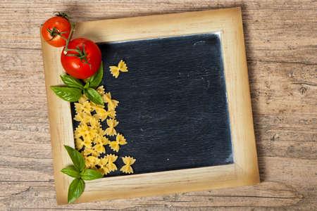 comida italiana: Comida Italiana. Pastas, tomates, albahaca en el pizarr�n negro. Enfoque selectivo