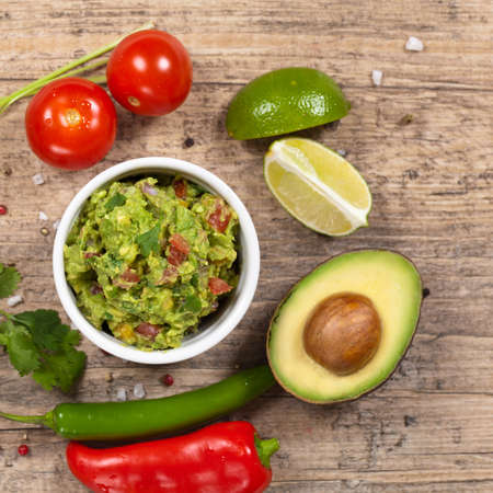 guacamole: Guacamole with avocado, lime, tomato and cilantro Stock Photo