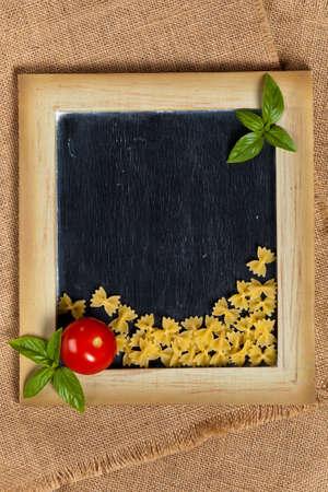 comida italiana: Comida italiana. Pastas, tomates, albahaca en el pizarr�n negro Foto de archivo
