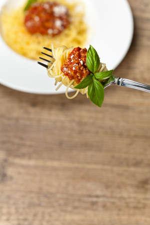 comida italiana: Comida italiana. Espaguetis a la bolo�esa con guarnici�n de albahaca Foto de archivo