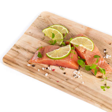 Fresh salmon fillet with oregano and lime slices. Selective focus. photo