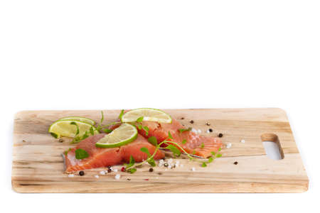 Fresh salmon fillet with oregano and lime slices. Selective focus photo