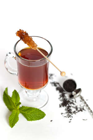 Tea with Mint Leaf and Candy Brown Sugar on a Sticks. Selective focus. photo